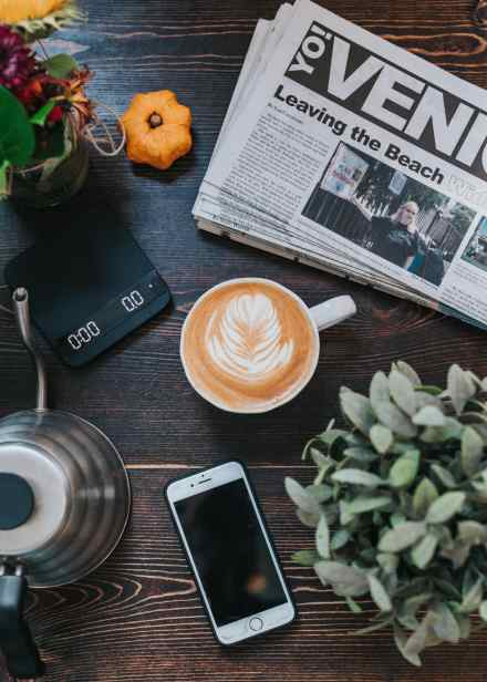 newspaper on table with latte and cellphone